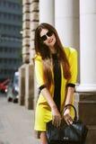 Portrait extérieur de la jeune belle dame heureuse marchant sur la rue Lunettes de soleil de port modèles et été jaune élégant Photo libre de droits