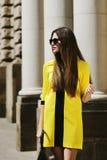 Portrait extérieur de la jeune belle dame marchant sur la rue Les lunettes de soleil de port modèles et l'été jaune élégant s'hab Images stock