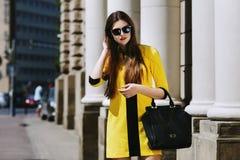 Portrait extérieur de la jeune belle dame marchant sur la rue Les lunettes de soleil de port modèles et l'été jaune élégant s'hab Image libre de droits