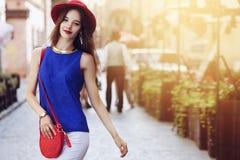 Portrait extérieur de la jeune belle femme de sourire heureuse posant sur la rue Chapeau et vêtements élégants de port modèles Fi Photos stock
