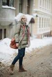 Portrait extérieur de la jeune belle fille heureuse posant sur la rue Vêtements chauds élégants de port modèles Chutes de neige m Photographie stock libre de droits