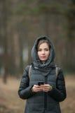 Portrait extérieur de manteau de port de belle jeune femme réfléchie avec le service de mini-messages de capot sur son smartphone images libres de droits