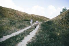 Portrait extérieur de marcher de jeunes couples enceintes dans le domaine avec le chien Vue arri?re photographie stock