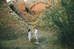Portrait extérieur de marcher de jeunes couples enceintes dans le domaine Vue d'arri?re photo stock