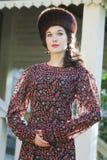 Portrait extérieur de mode de jeune femme dans l'habillement médiéval russe de style avec le chapeau de Cosaque de fourrure Images stock