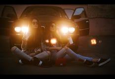 Portrait extérieur de mode de vie d'une paire de filles assez jeunes de meilleurs amis utilisant des lunettes de soleil, portant  Image stock