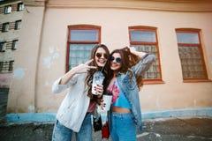 Portrait extérieur de mode de vie d'une paire de filles assez jeunes de meilleurs amis utilisant des lunettes de soleil, portant  Images stock