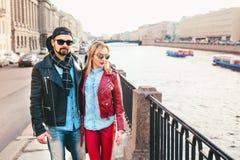 Portrait extérieur de mode des couples élégants marchant sur le coucher du soleil regard noir en cuir de port de petit pain de la Photos libres de droits