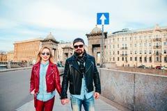 Portrait extérieur de mode des couples élégants marchant sur le coucher du soleil regard noir en cuir de port de petit pain de la Image libre de droits