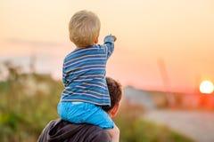 Portrait extérieur de père et de fils à la lumière du soleil de coucher du soleil Photo libre de droits