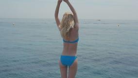Portrait extérieur de vacances d'été de la femme blonde de sourire heureuse assez jeune posant dans le bikini sur le fond bleu de banque de vidéos