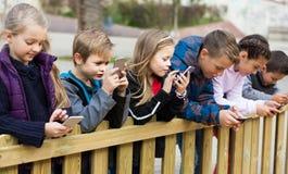 Portrait extérieur des filles et des garçons jouant avec des téléphones Images stock