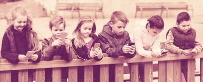 Portrait extérieur des filles et des garçons jouant avec des téléphones Images libres de droits
