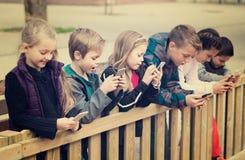 Portrait extérieur des filles et des garçons jouant avec des téléphones Photos libres de droits