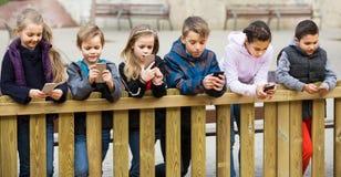Portrait extérieur des filles et des garçons jouant avec des téléphones Photographie stock