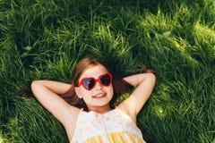 Portrait extérieur des lunettes de soleil en forme de coeur de port de fille assez petite Photos libres de droits