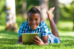 Portrait extérieur du garçon de noir d'étudiant à l'aide d'un comprimé tactile - A Photos stock