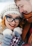 Portrait extérieur sensible d'hiver des couples heureux L'homme bel est étreignant et tenant des mains de son amie Photographie stock