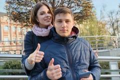 Portrait ext?rieur des couples montrant l'ok de signe de geste Jeune homme et femme avec le smartphone dans des ?couteurs, heure  photo stock