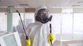 Portrait of the exterminator in overalls with a sprayer