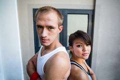Portrait of extreme athletes standing back to back with arms crossed Royalty Free Stock Photography