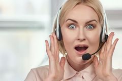 Portrait of extremely surprised woman with headset. royalty free stock photo