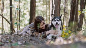 Portrait of eye-catching girl lying in the forest with her dog stock video footage