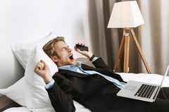 Portrait f attractive bearded businessman lying in hotel room, holding phone and laptop computer, yawning and going to royalty free stock photos