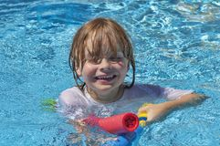 Portrait of the face and chest of a boy 7 lying in the pool and playing with his water gun royalty free stock image
