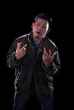 Portrait face of young asian man acting like a rocker man standi. Ng against dark background Royalty Free Stock Images