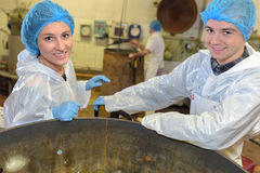 Portrait factory operatives stood by vat Stock Photo