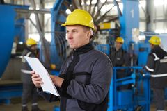 Portrait of factory worker holding paper clipboard. Young engineer in uniform and hardhat taking notes working at metal production factory, copy space Royalty Free Stock Image