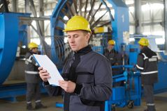 Portrait of factory worker holding paper clipboard. Young engineer in uniform and hardhat taking notes working at metal production factory, copy space Stock Image