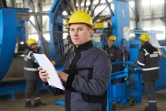 Portrait of factory worker holding paper clipboard. Young engineer in uniform and hardhat taking notes working at metal production factory, copy space Stock Photography