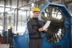 Portrait of factory worker holding paper clipboard. Young engineer in uniform and hardhat taking notes working at metal production factory, copy space Stock Photos