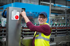 Portrait of factory worker operating machine. At drinks production factory Stock Photo