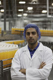 Portrait of factory worker standing with arms crossed at bottling plant Royalty Free Stock Image