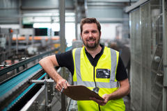 Portrait of factory worker standing with clipboard. In factory Stock Image
