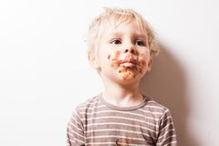 Boy eated chocolate, funny dirty smiled face royalty free stock photography