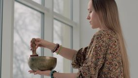 Portrait of fair-skinned young woman playing the singing bowl stock footage