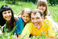 Portrait of family. Portrait of happy family lying on the grass and looking at camera Royalty Free Stock Photography