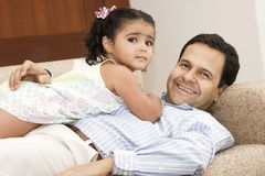 Portrait of family. Dad playing with his daughter at home royalty free stock images