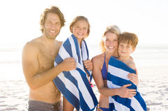 Portrait of family at beach. Family with their children draped in towel at beach after swim. Portrait of smiling parents with daughter and son after swimming Royalty Free Stock Photo