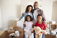 Portrait Of Family Carrying Boxes Into New Home On Moving Day royalty free stock image