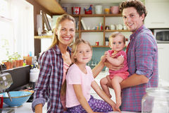 Portrait Of Family Cooking Meal In Kitchen Together Stock Photo