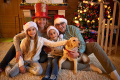 Portrait family and dog sitting by Christmas tree Stock Photos