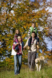 Portrait of family and dog walking through field Stock Photography