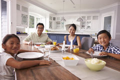 Portrait Of Family Eating Meal At Home Together Stock Images