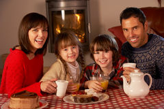 Portrait Of Family Enjoying Tea And Cake. By Cosy Log Fire Stock Photography