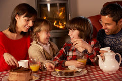 Portrait Of Family Enjoying Tea And Cake. By Cosy Log Fire Royalty Free Stock Photography